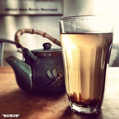 Freshly made glass of tea with ceramic tea pot on a wooden table