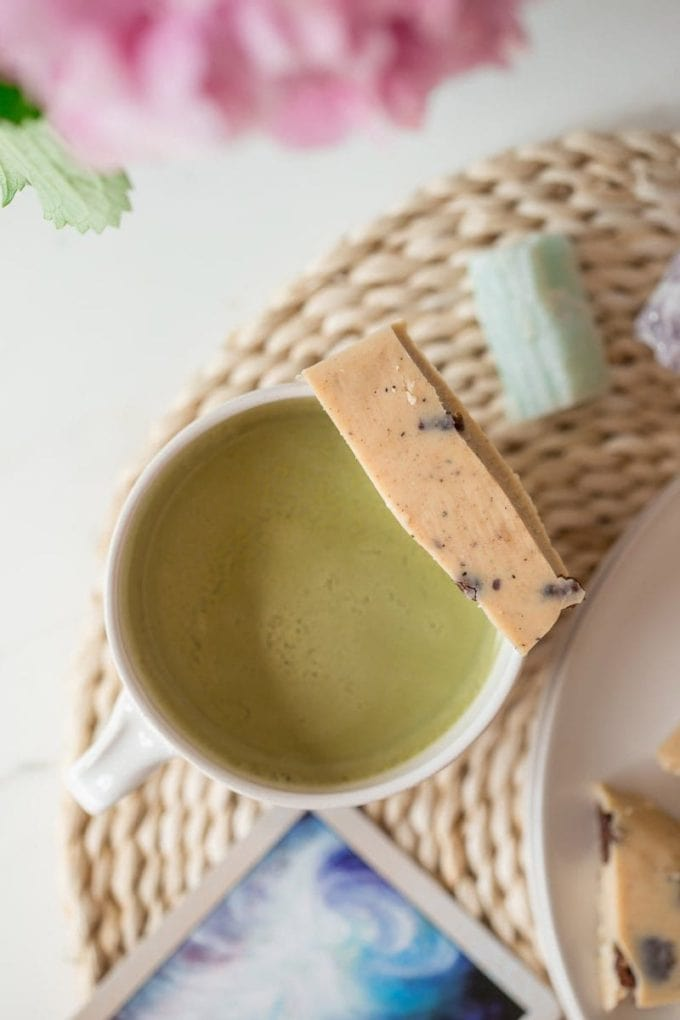 Birds eye view of a mug of matcha tea with a shard of cookies and cream bark resting over the top