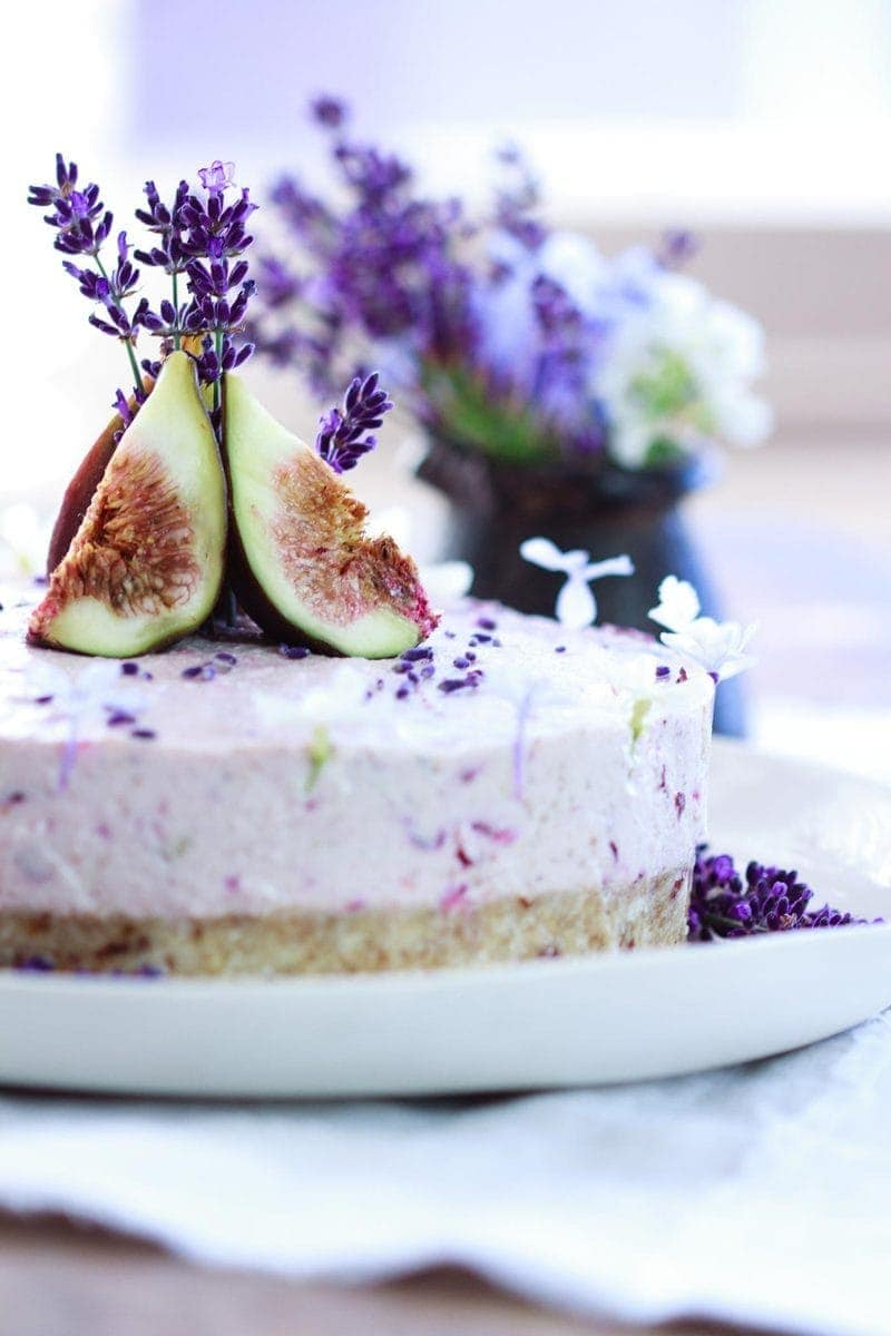 A pale purple coloured Lavender Cake made with raw food ingredients, decorated with quartered figs and fresh lavender flowers