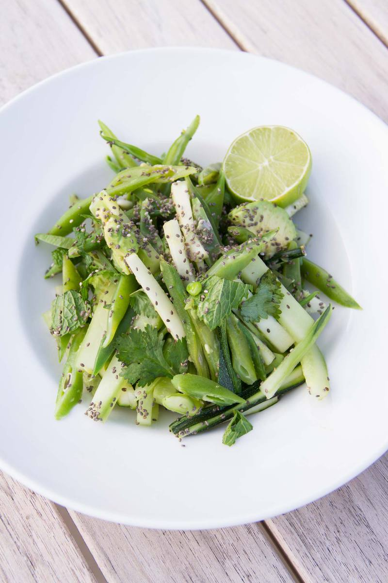 Plate of fresh green vegetables topped with chia seeds and lime on an outdoor table