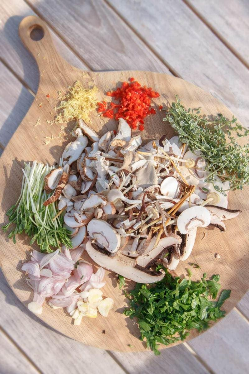A wooden board filled with ingredients used in a mushroom dish - mixed varieties of mushrooms, shallot, ginger, chilli, thyme, garlic