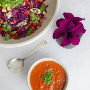 Bowl of colourful raw salad with a bright orange dressing on kitchen table