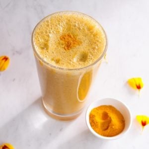 Bright yellow smoothie in a glass with a dusting of turmeric powder on top