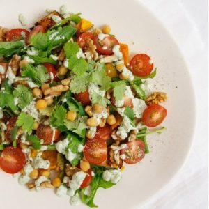 Close up of a plate of salad - pumpkin and chickpea with fresh herbs and tomatoes on top