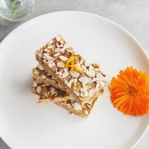 Raw bars stacked high on a plate with a calendula flower beside it as decoration