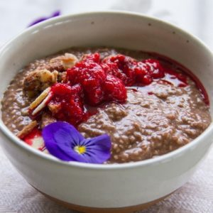 Close up of a bowl full of chocolatey chia pudding with raspberry jam on top