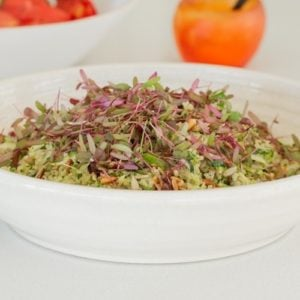 Close up of a warm quinoa salad in a white bowl, finished with a green dressing, toasted seeds and herbs
