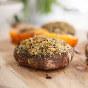 Baked mushrooms stuffed with avocado, herbs and breadcrumbs on a wooden chopping board on the kitchen bench