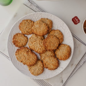 Stack of healthy ANZAC biscuits on a plate with a hot drink