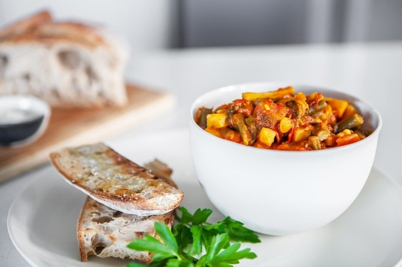 A bowl of winter vegetable stew on the kitchen bench, with a loaf of toasted, garlicky sourdough in the background