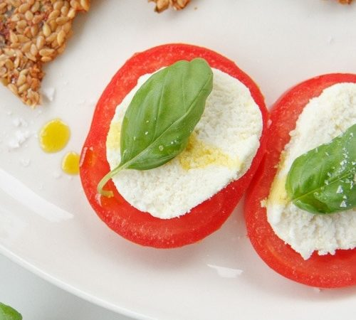 Close up of raw vegan mozzarella slices on thick sliced heirloom tomatoes topped with basil