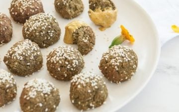Golden yellow tahini sauce drizzled over baked falafels on a plate