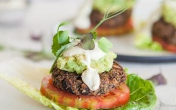 A vegan burger patty encased in a cos lettuce leaf in place of a bread bun, with tomato and dairy free aioli