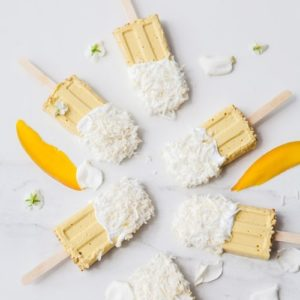 6 mango popsicles dipped in coconut yoghurt spread out over a marble counter