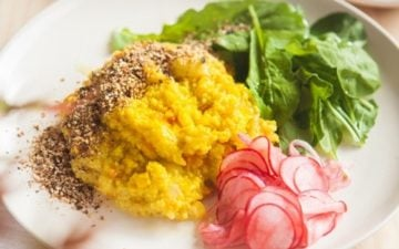 Plate filled with millet stained yellow from turmeric, with fresh greens and pickled radish