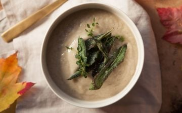 Creamy bowl of soup seasoned with fresh herbs, a golden spoon beside it