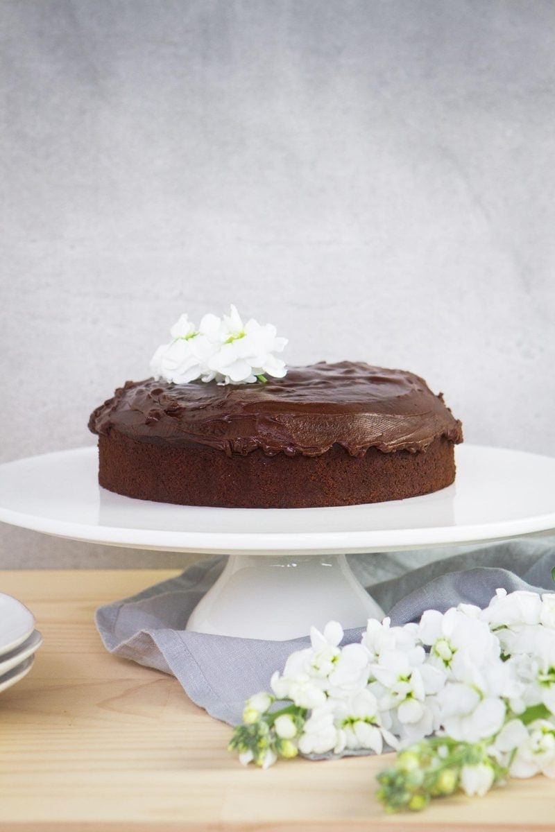 Best Ever Gluten Free Vegan Chocolate Cake with Ganache  on a white cake stand with white flowers