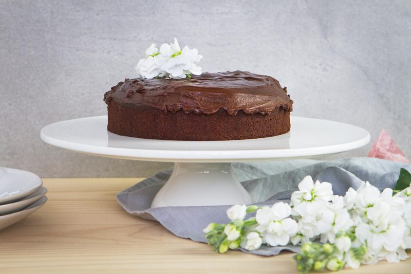 Best Ever Gluten Free Vegan Chocolate Cake with Ganache presented beautifully on a cake stand
