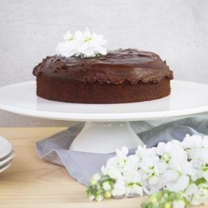 Beautiful gluten free chocolate cake covered in icing on a white cake stand surrounded by flowers