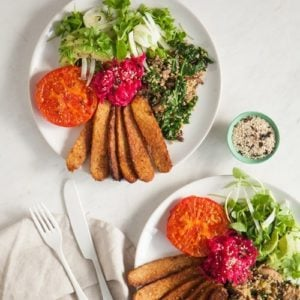Two plates on a marble counter filled with marinated tempeh, roast tomatoes and salad greens