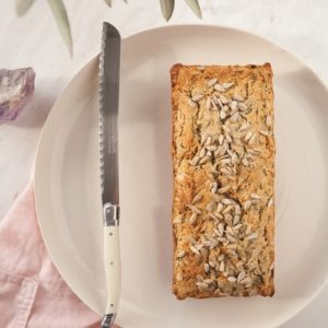 Loaf of healthy zucchini bread freshly baked on a plate with a knife ready to serve