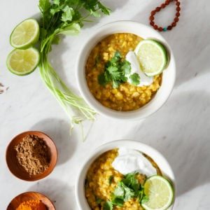 Two white bowls of Kitchari on a marble sounter surrounding by fresh lime, cilantro and spices