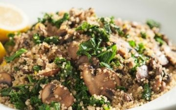 Close up of warm quinoa salad in a white bowl with fresh herbs
