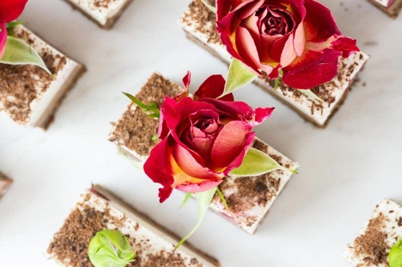 Close up of a Raw Black Forest Slice dusted with chocolate and finished with red roses