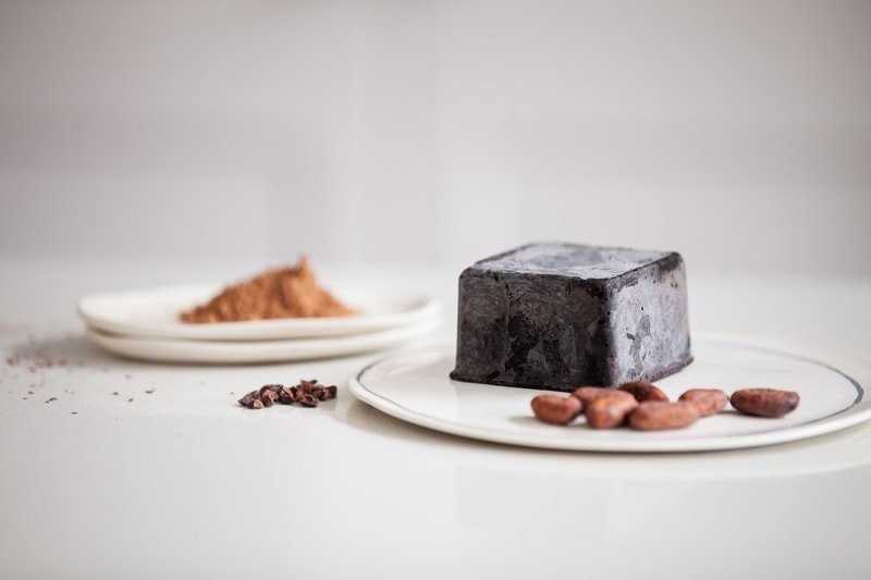 Benefits of Cacao: block of raw cacao paste and raw cacao beans, nibs and powder