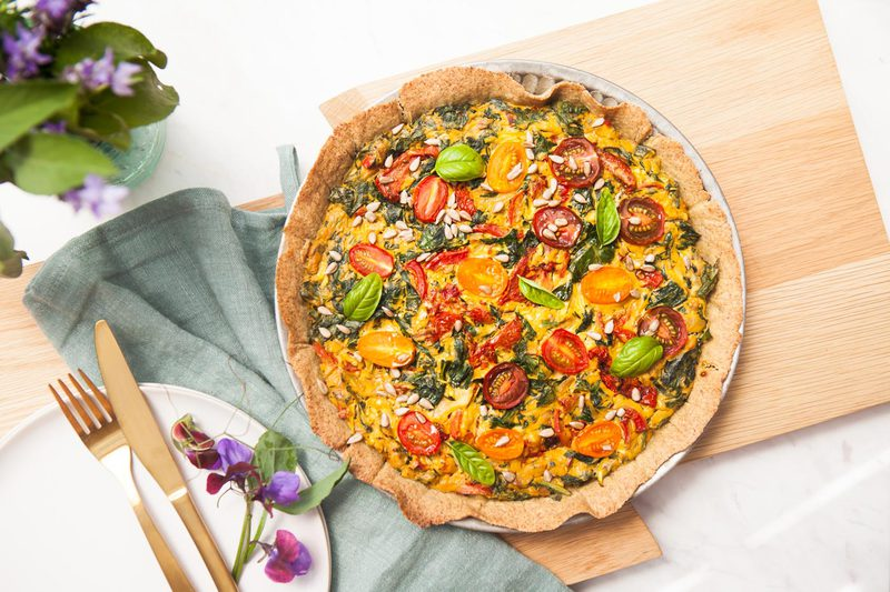 A vegan gluten free quiche on a wooden board with a rustic jar of wildflowers in an outdoor setting