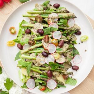 Plate of vegan salad nicoise with asparagus and lentils on an oak chopping board