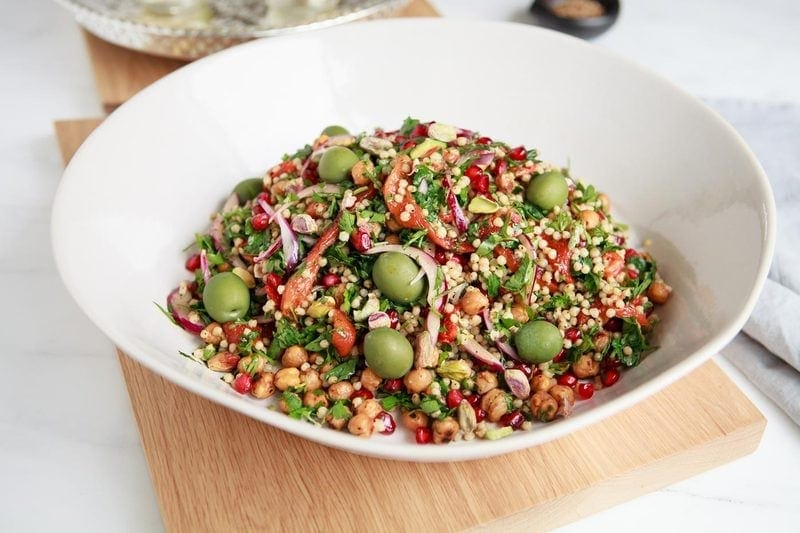 A colourful Sorghum Salad filled with green olives and pistachios, and red pomegranate, capsicum and onion