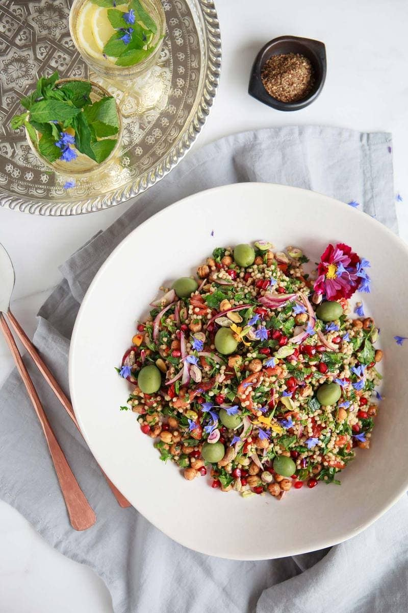 Chickpea Sorghum Salad in a large serving bowl with purple cornflowers scattered over the top