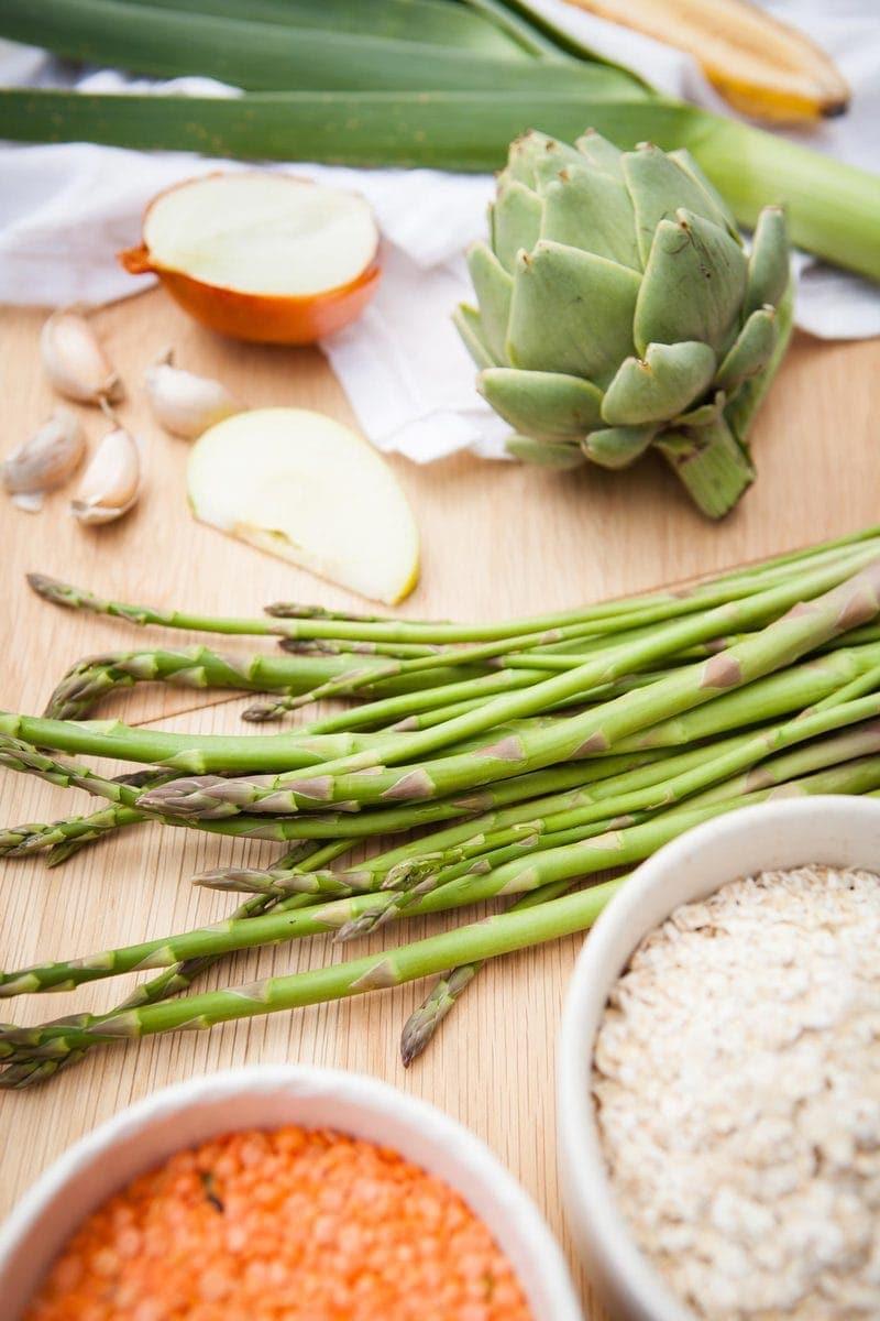 Close up of a few prebiotic-rich foods such as asparagus, globe artichoke and garlic.