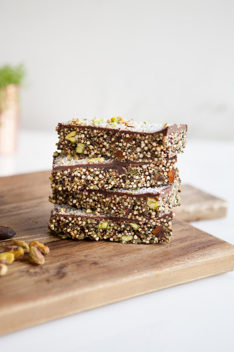 Stack of four popped quinoa bars with apricot and chocolate on a wooden board ready to enjoy