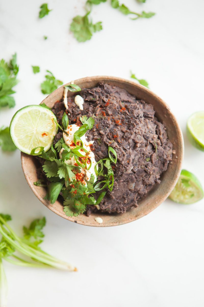 Refried Black Beans recipe made from scratch in a rustic bowl with lime, coconut and herbs over the top