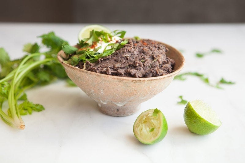Homemade Refried Black Beans in a Mexican ceramic bowl garnished with lime and scallions
