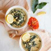 Two bowls of chunky soup containing white beans, lemon, garlic and kale, sitting on white marble and a pink linen napkin