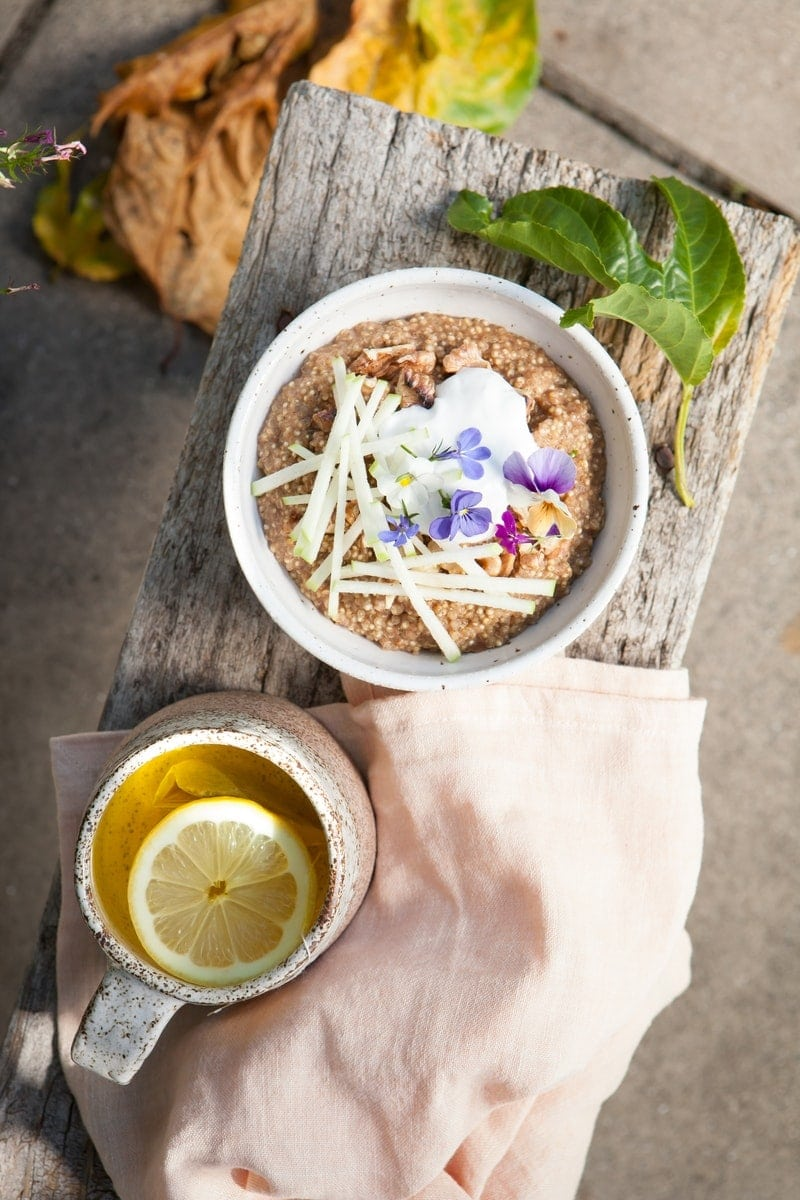 Coconut Quinoa Porridge and a mug of lemon ginger tea on a rustic stool outdoors ready to serve