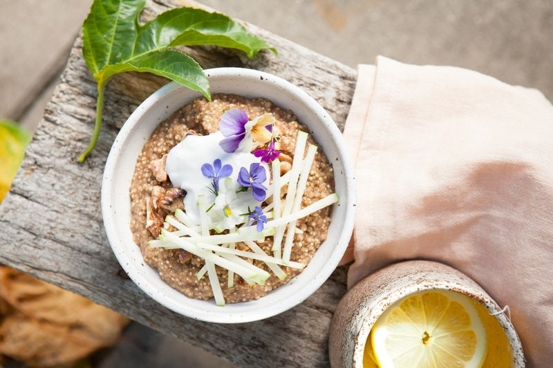 Speckled ceramic bowl of Quinoa Porridge on a rustic stool, topped with coconut, apple and pansies