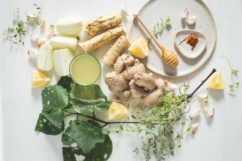 Flat lay of ingredients for a herbal immune tonic - also known as fire cider
