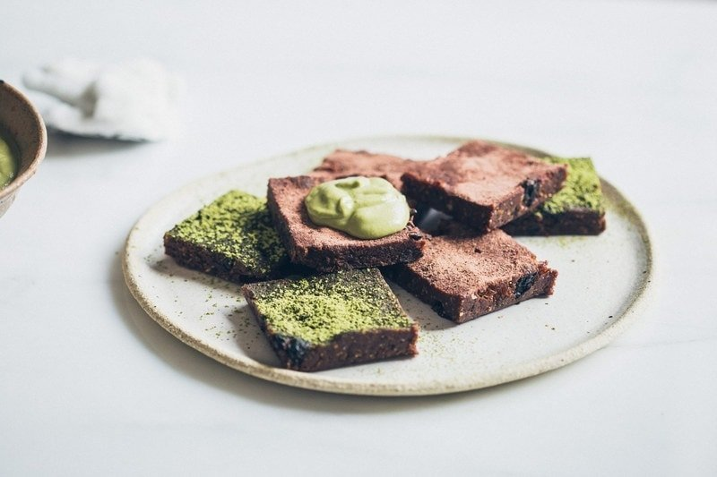 Ceramic plate filled with a stack of raw brownies dusted with matcha