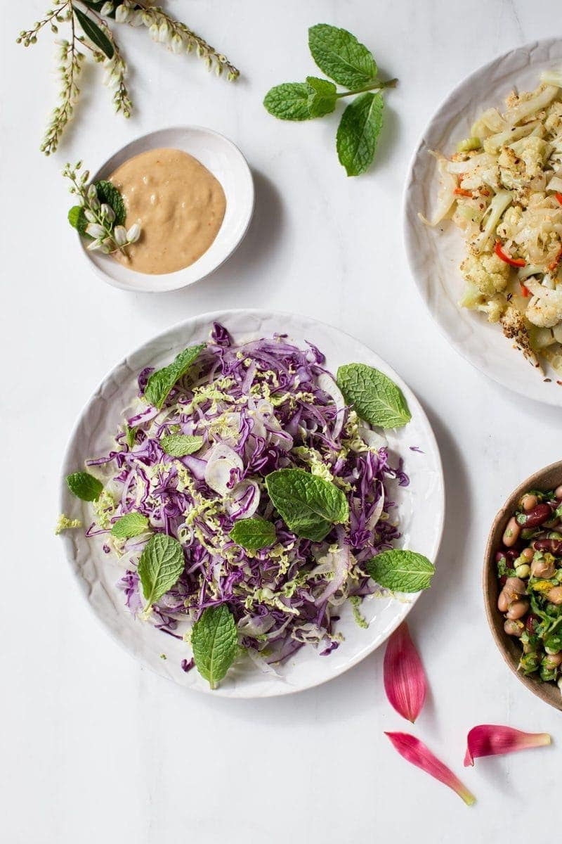 Dinner spread featuring healthy slaw with a side of creamy miso tahini dressing