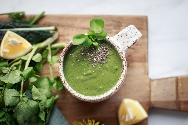 Bright green watercress soup in a rustic ceramic mug with a sprinkle of chia seeds on top