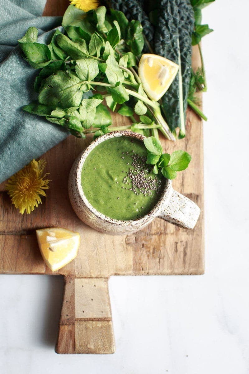 Mug of watercress soup on a wooden board surrounded by fresh ingredients