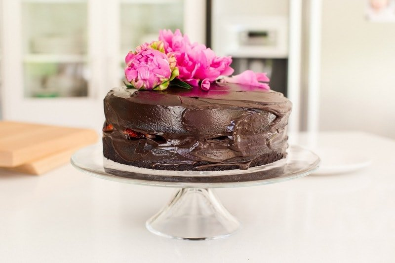 Close up of double layer chocolate cake with strawberries in between, thick coating of chocolate frosting and a pink flower on top