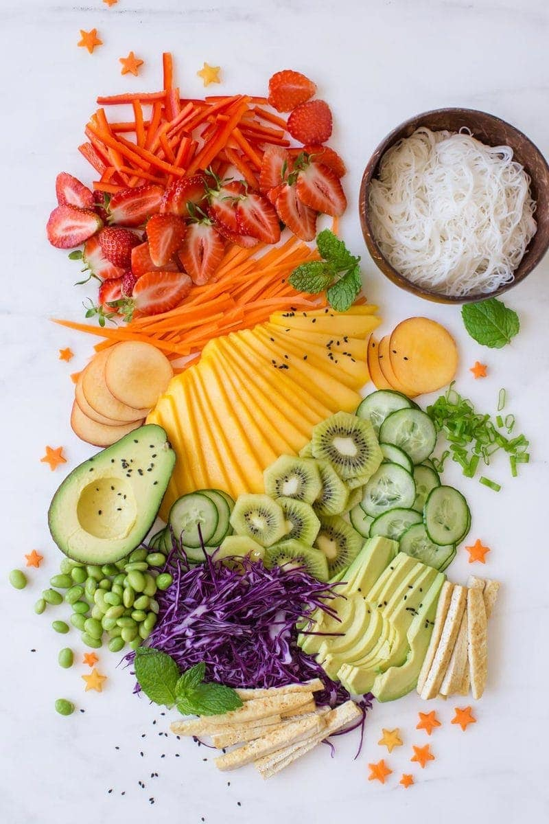 A rainbow of finely sliced fresh fruits and vegetables laid out decoratively on a marble counter, destined for summer rolls