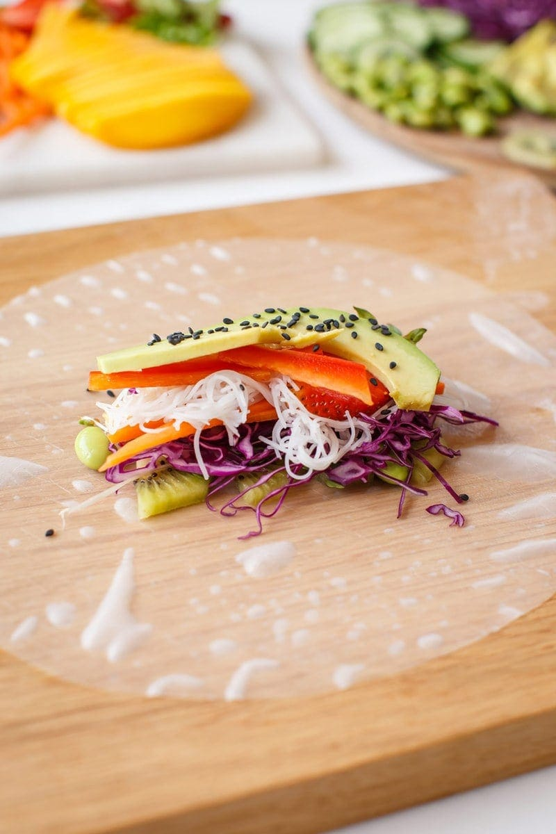A rice paper wrapper with freshly sliced vegetables and avocado ready to be rolled, on a wooden board