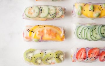 Close up of summer rice paper rolls filled with a rainbow of fruits and vegetables on marble counter