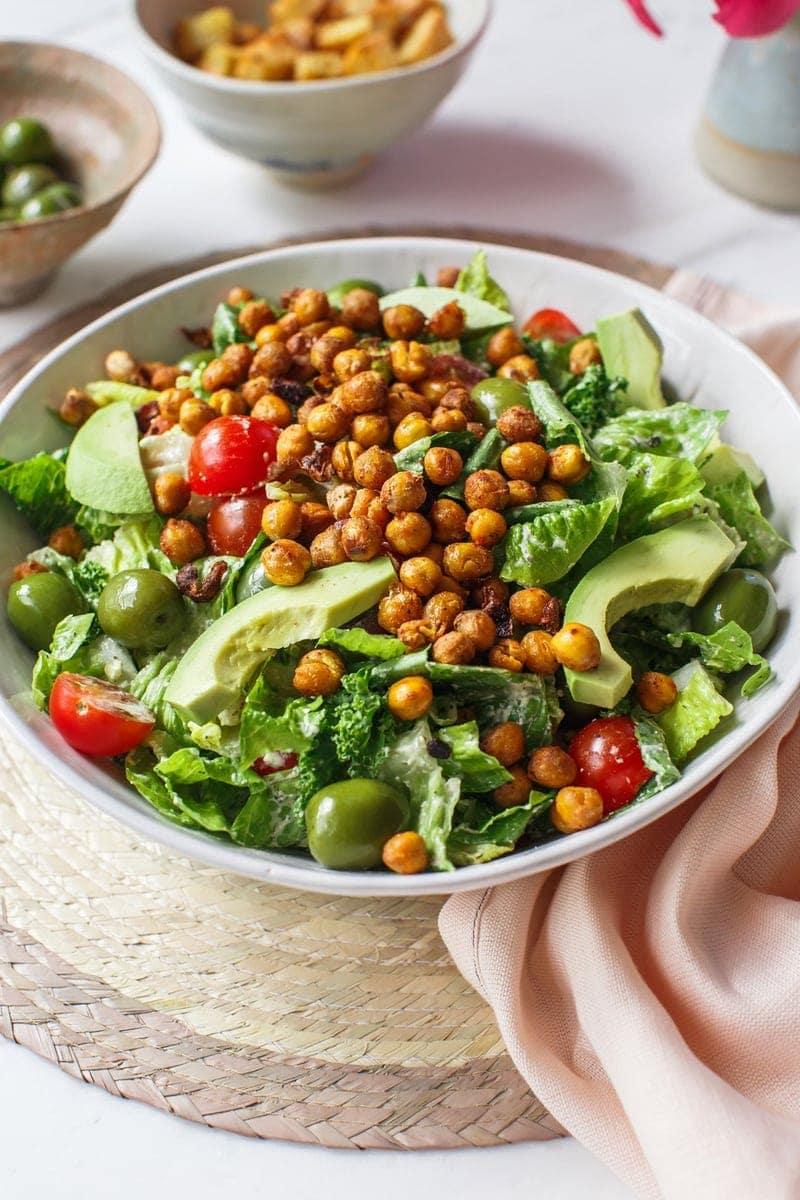 Large serving bowl of vegan Caesar salad on the kitchen bench